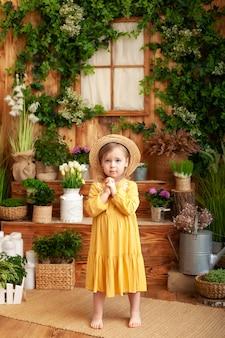 Enfant priant. petite fille main priant, mains jointes dans le concept de prière pour la foi, la spiritualité et la religion. une petite fille vaut dans l'arrière-cour d'une maison en bois, autour de plantes vertes et de fleurs.