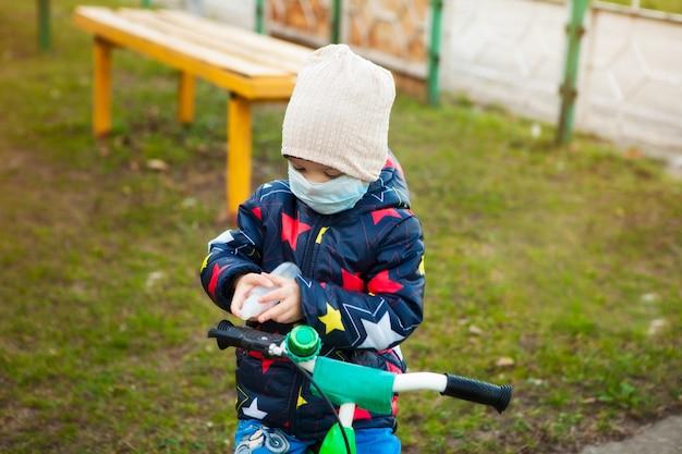 Enfant en promenade dans un parc de la ville dans un masque médical à vélo. traitement des mains avec antiseptique. marcher dans la rue pendant la période de quarantaine de la pandémie de coronavirus dans le monde