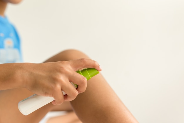 L'enfant pulvérisant des insectes moustiques mord sa jambe