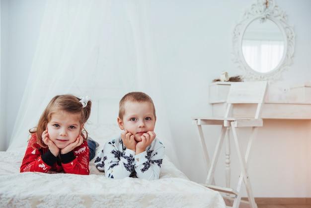 Enfant en pyjama chaud et doux jouant au lit