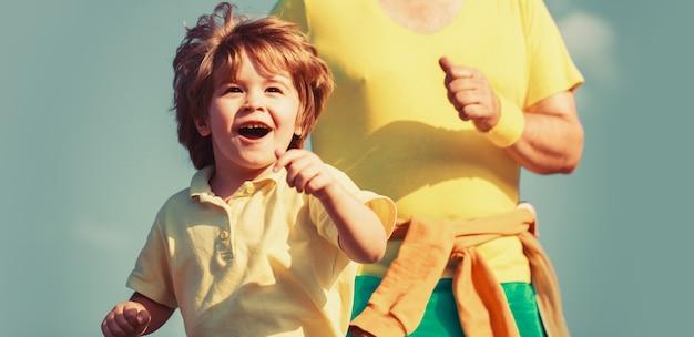 Enfant qui court dans le stade. kid courir à l'extérieur. jogging pour enfant. père et fils font du sport et courent. activité sportive saine pour les enfants. sport pour les enfants, enfant actif qui court. notion de famille saine.
