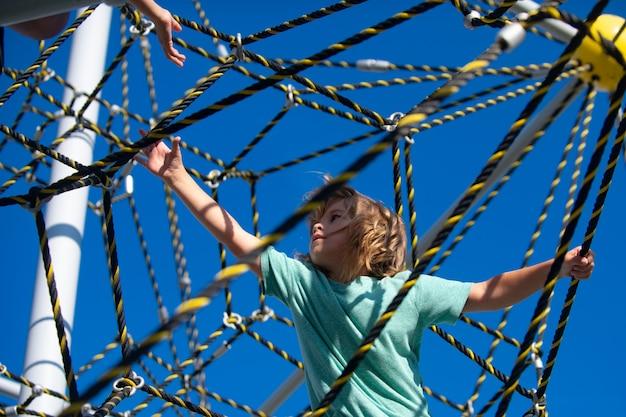 Enfant qui grimpe sur le net. les enfants font du sport.