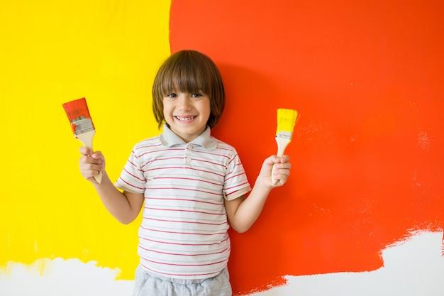 Enfant qui peint le mur de la maison en couleurs