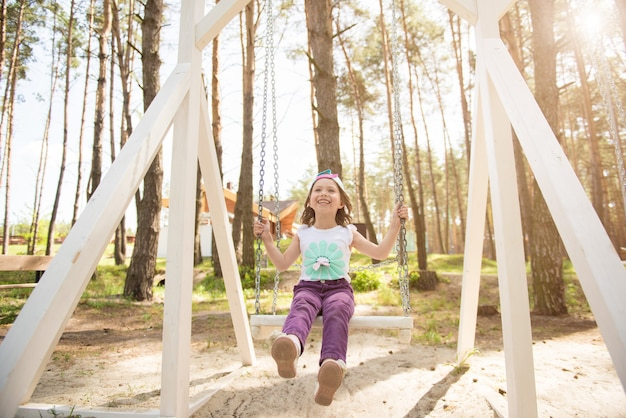 Enfant qui rit sur la balançoire dans le parc d'été