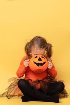 Enfant à la recherche de bonbons en pot citrouille halloween vertical jaune isolé