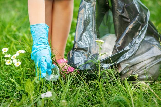 L'enfant recueille les déchets en plastique de l'herbe jetant des ordures dans un sac à ordures dans le parc