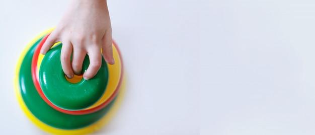 L'enfant recueille une pyramide. détails du jouet dans les mains.