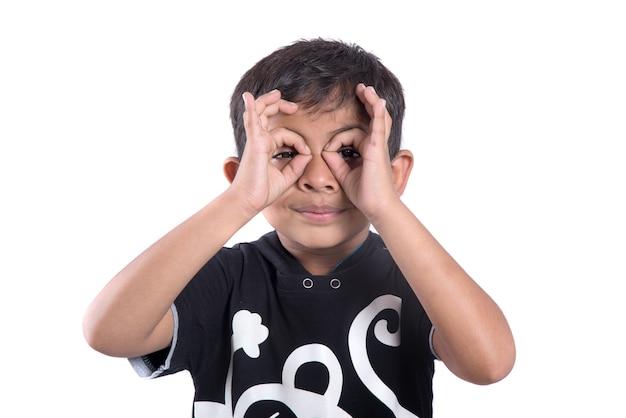 Enfant regardant la caméra à travers les doigts en geste ok