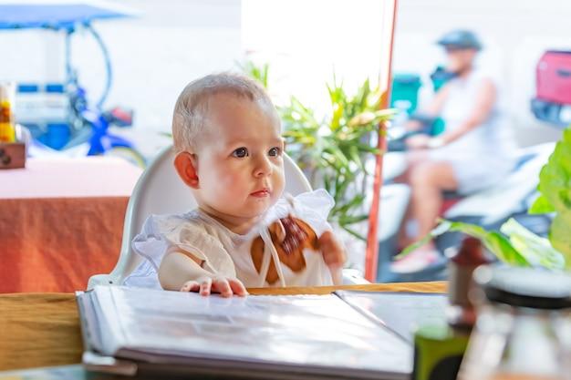 L'enfant regarde attentivement devant lui. une petite fille est assise sur une chaise haute de bébé dans un café de la rue.