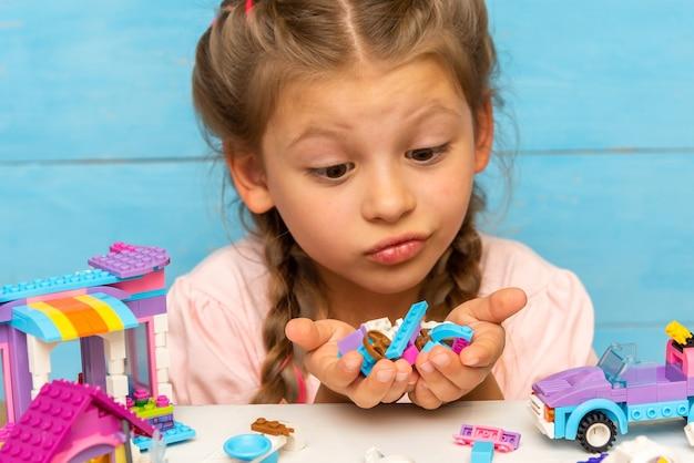 L'enfant regarde beaucoup de détails du constructeur sur un fond bleu clair.