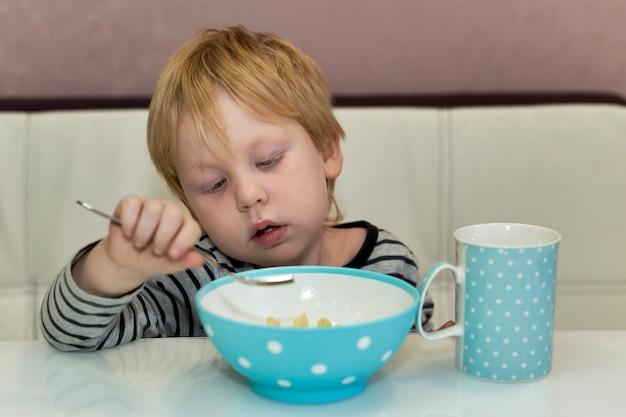 L'enfant regarde la fourchette qu'il mange dans l'assiette alors qu'il était assis à table