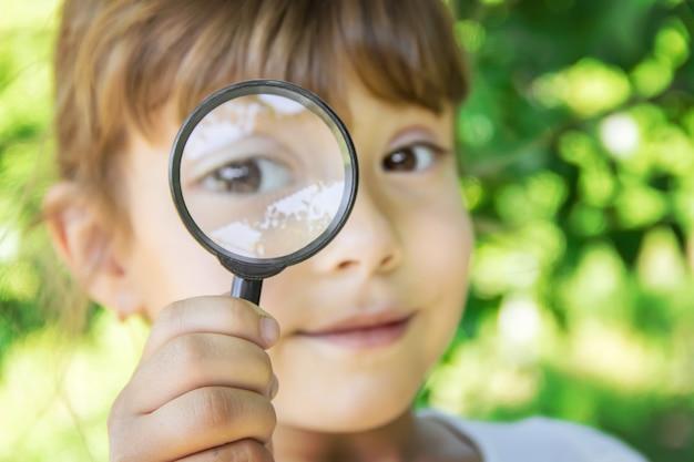 L'enfant regarde à la loupe. augmenter. mise au point sélective.