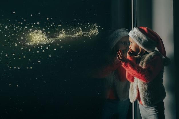 L'enfant regarde par la fenêtre le noël de jésus-christ.