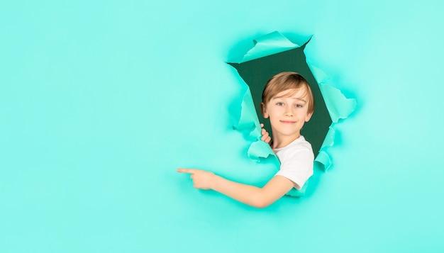 L'enfant regarde à travers le trou. un garçon blond regarde à travers du papier déchiré. garçon dans un trou de papier rouge pointant avec le doigt de côté. garçon souriant regardant à travers le trou dans le mur de papier. enfant surpris faisant un trou dans le papier.