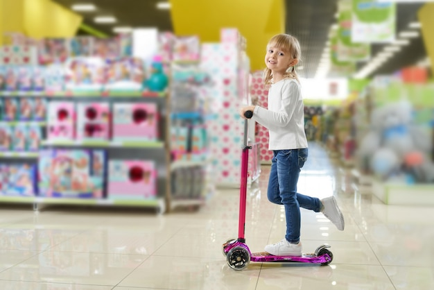 Enfant, regarder appareil-photo, et, rire, quoique, équitation, scooter