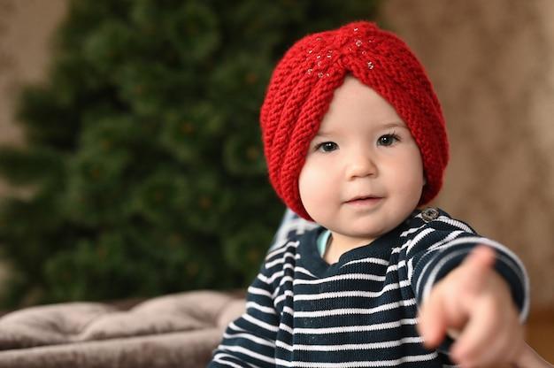 L'enfant rit et montre un doigt. l'enfant a 0-1 ans. un petit enfant montre un doigt d'une main. portrait d'enfant d'un an.