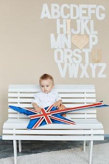 Enfant rock drôle avec guitare rock, petit garçon à la mode en chemise blanche est assis sur un banc et posant
