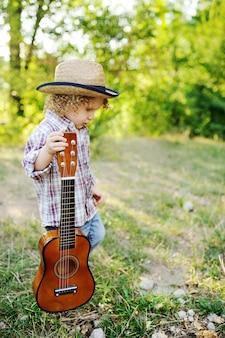 Enfant rousse bouclé dans un chapeau de paille