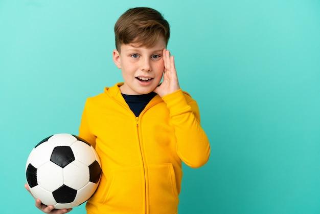 Enfant rousse jouant au football isolé sur fond bleu criant avec la bouche grande ouverte