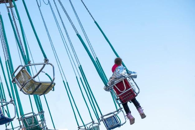 Enfant s'amusant à cheval sur un carrousel à chaînes dans le parc d'attractions b