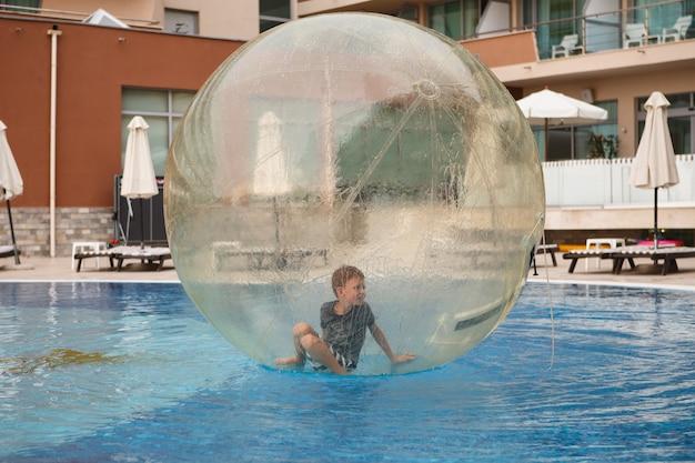 L'enfant s'amuse à l'intérieur d'un grand ballon en plastique sur l'eau de la piscine de la station balnéaire. petit garçon à l'intérieur de la grande boule transparente gonflable en cours d'exécution et s'amuser.