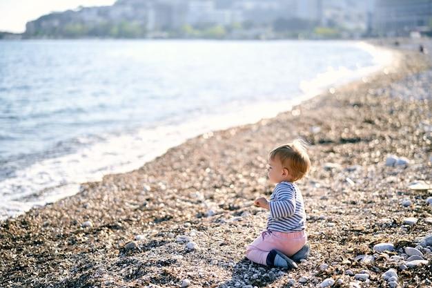 L'enfant s'assied sur ses genoux sur une plage de galets et regarde la mer