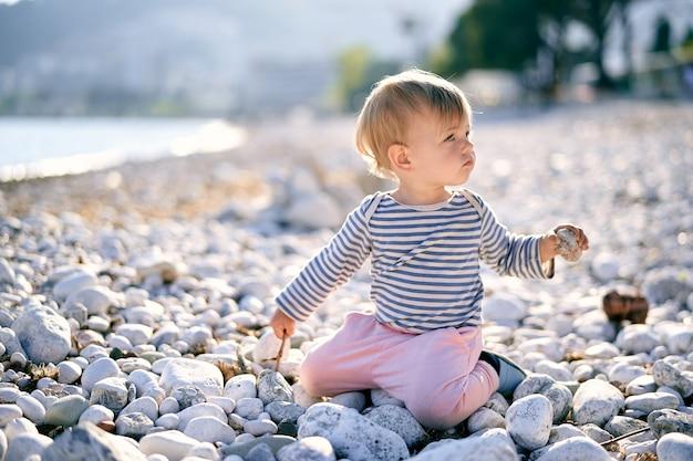 L'enfant s'assied sur ses genoux avec sa tête tournée sur une plage de galets et tient un caillou dans sa main