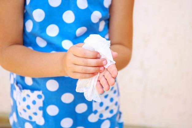 L'enfant s'essuie les mains avec un chiffon humide.