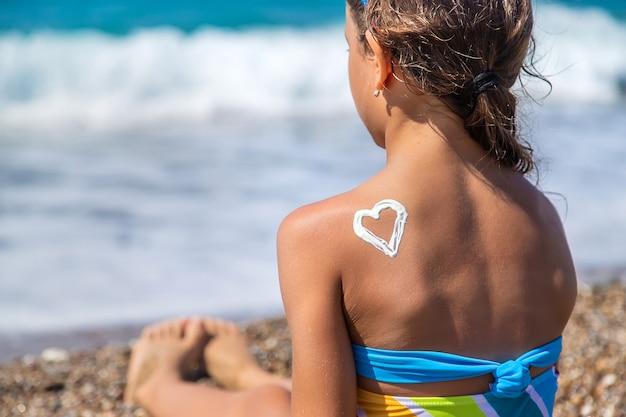 L'enfant s'étale de la crème solaire sur le dos. mise au point sélective. enfant.