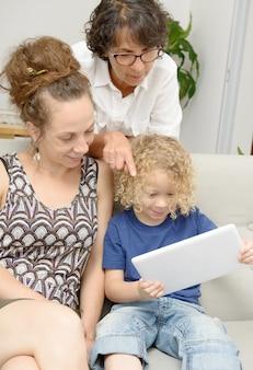 Enfant et sa mère avec grand-mère jouent avec tablette