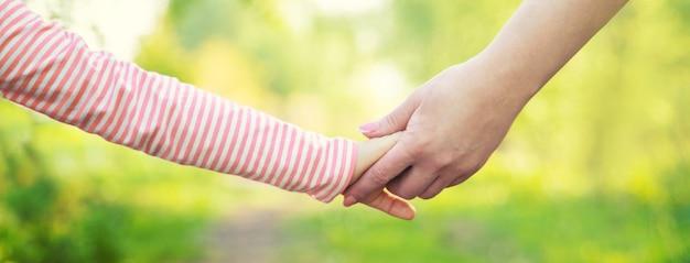 Un enfant avec sa mère passe par la main
