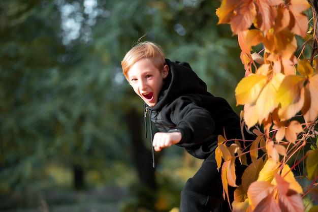 Un enfant saute de derrière un arbre avec des feuilles d'automne jaunes et des cris