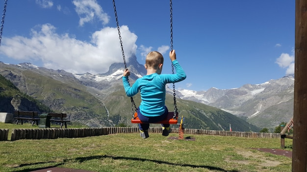Enfant se balançant dans un parc avec vue sur le cervin