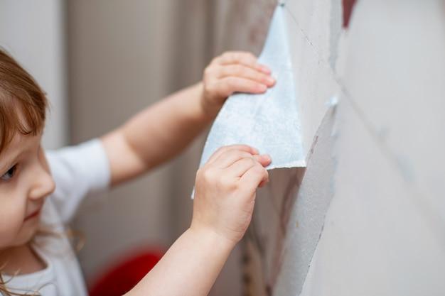 L'enfant se déchire papier peint