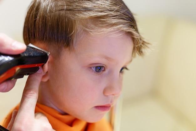 Enfant se faisant couper les cheveux au salon de coiffure
