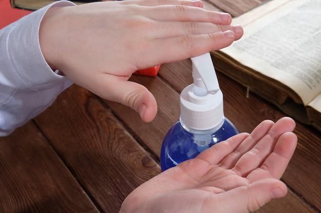 L'enfant se lave les mains avec du gel à la table