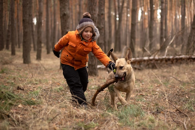 Un enfant se promène avec un chien dans la forêt.