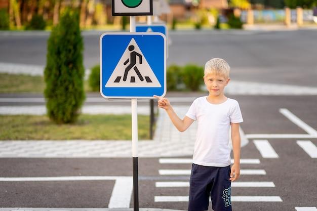 Un enfant se tient à un signe de passage pour piétons et le montre avec son doigt
