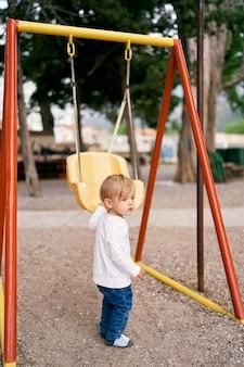 L'enfant se tient sur le terrain de jeu près de la balançoire