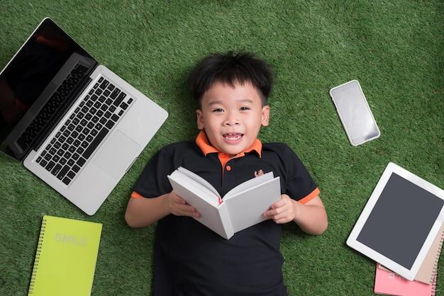 Enfant de sept ans lisant un livre allongé sur l'herbe