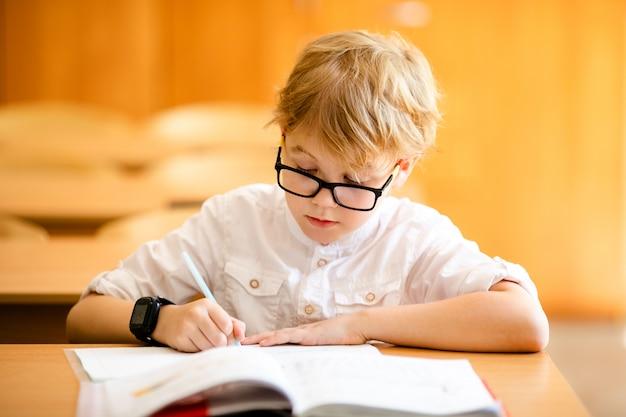 Enfant de sept ans portant des lunettes écrivant ses devoirs à l'école