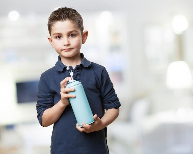 Enfant sérieux avec une bombe aérosol