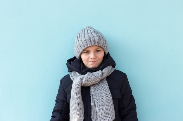 Enfant sérieux drôle prêt pour les vacances d'hiver. garçon à la mode en bonnet gris d'hiver et écharpe debout contre le mur bleu.