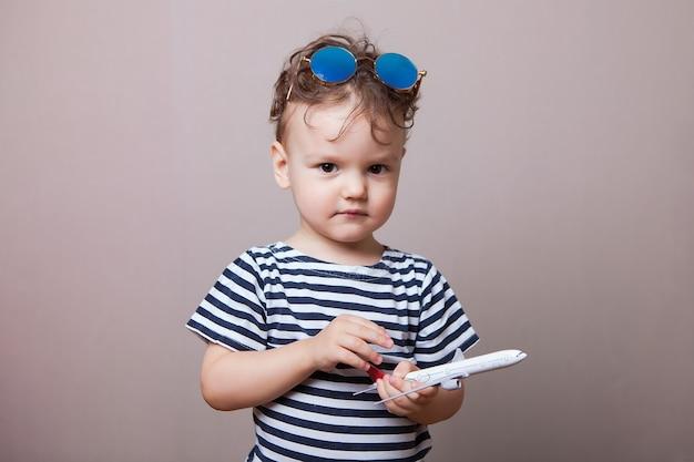 Enfant sérieux avec un modèle d'avion dans les mains.