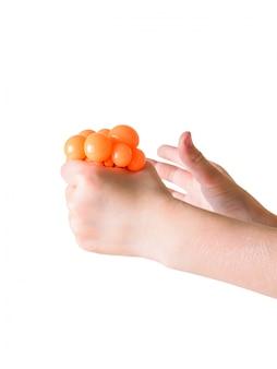 L'enfant serre le jouet antistress main isolé sur fond blanc. un appareil apaisant. traitement des troubles mentaux.