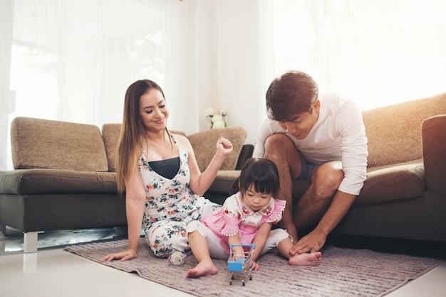 Enfant avec ses parents jouant au sol dans le salon