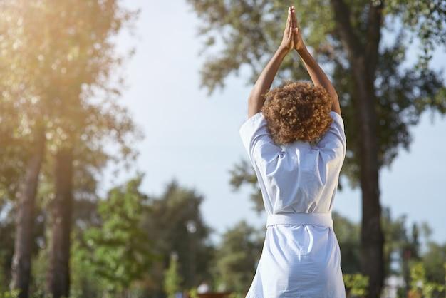 Enfant de sexe féminin afro-américain faisant des exercices de méditation à l'extérieur
