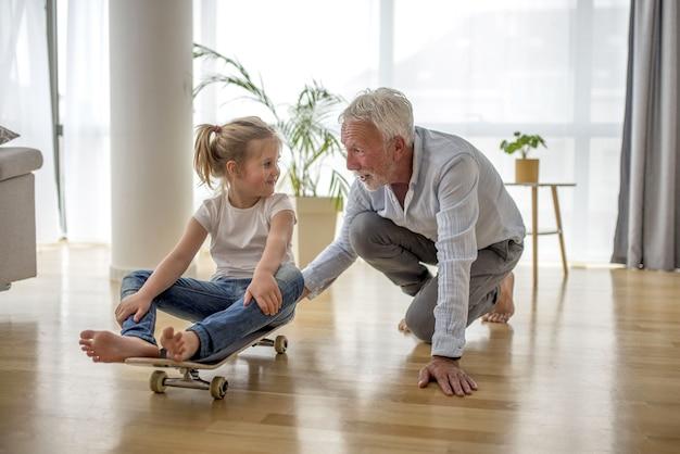 Enfant de sexe féminin blonde caucasien assis sur une planche à roulettes son grand-père la poussant à l'intérieur d'une maison