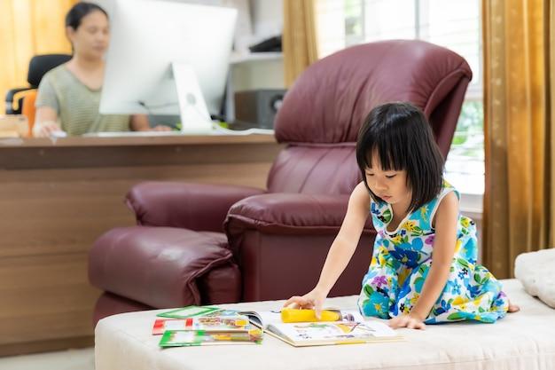 Enfant de sexe féminin lisant comme enseignement à domicile avec maman travaillant