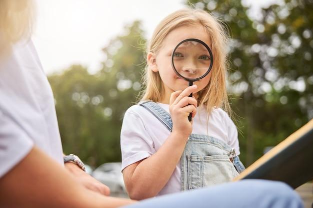 Enfant de sexe féminin mignon posant à l'appareil photo à l'extérieur